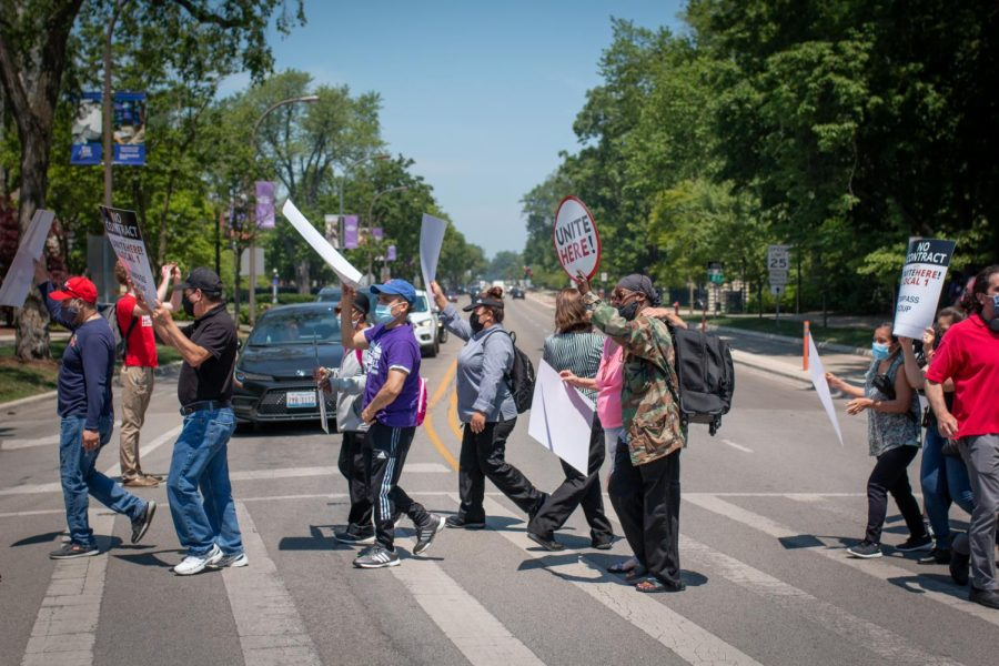 """A group of workers crosses the street holding signs that read """"UNITE HERE!"""""""