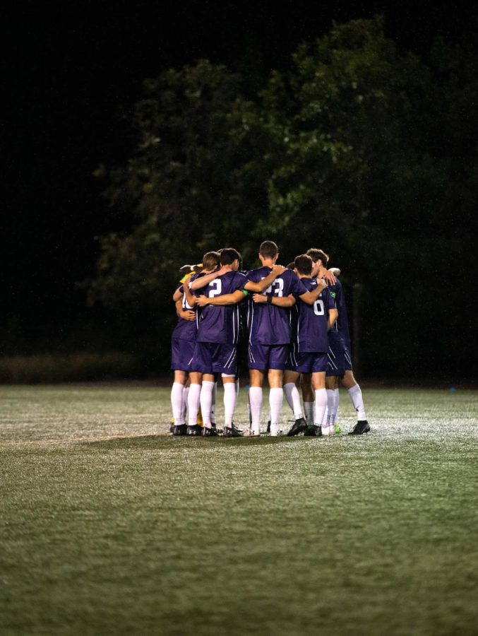 Soccer players in purple jerseys and shorts wearing white socks and black cleats embrace on a green field with trees in the background.