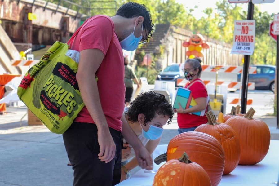 Two participants look at a table with white tablecloth lined up with five carved pumpkins. One participant is gesturing to one particular pumpkin while the other participant bends down to closely examine the same pumpkin.