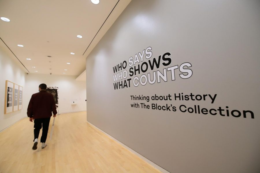 """A grey wall reads """"Who Says, Who Show, What Counts: Thinking about History with the The Block's Collection."""" A person walks along the wall, away from the camera. A few frames of artwork are visible in the background."""