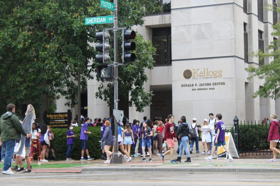 """Several students waiting in line at a tan building labeled """"Donald P. Jacobs Center."""" Others walk across the street and walk in the direction of the building."""