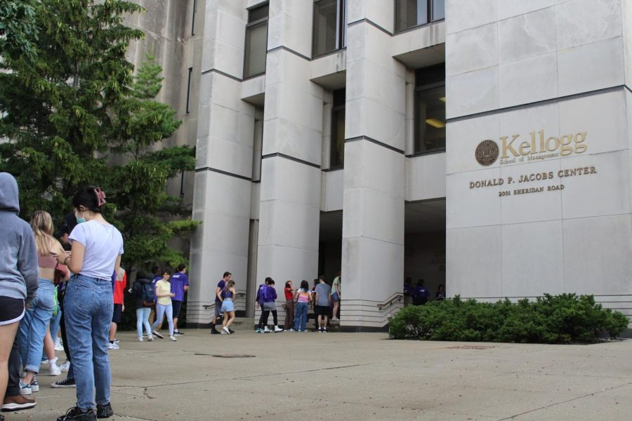"""Students stand in line behind a tan building labeled with the """"Donald P. Jacobs Center"""" in gold capital letters."""