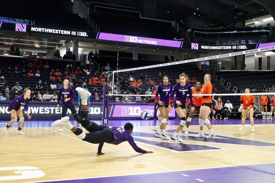 Player in purple jersey dives to floor to hit ball.
