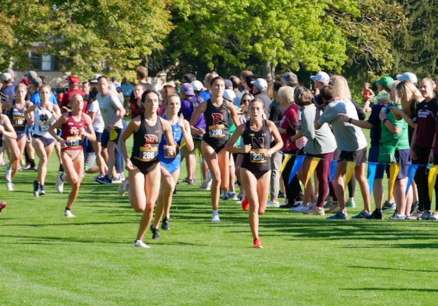 A runner with blonde hair wearing a black jersey with a big 'N' on it competes among a crowded race field