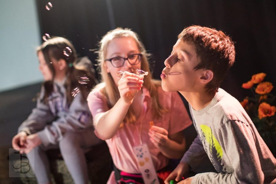 A girl leans over to let a boy blow bubbles out on a stage with a spotlight on him.
