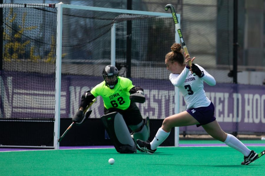 Girl with curly brown hair in bun in white bends down with field hockey stick in hand