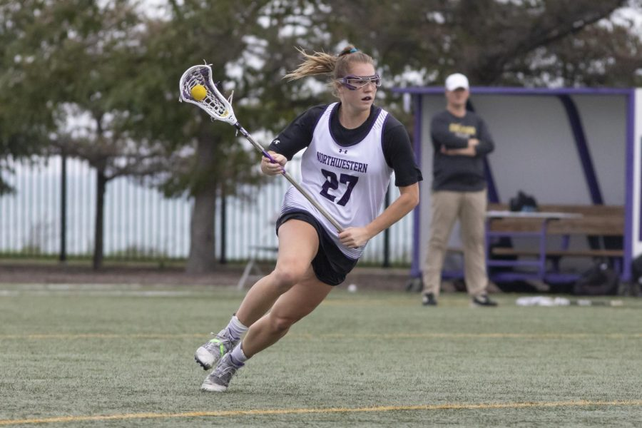 A girl with brown hair wearing a white jersey with the number '27' over a black top with white shorts and white cleats runs down a green field holding her white lacrosse stick with a ball in it.