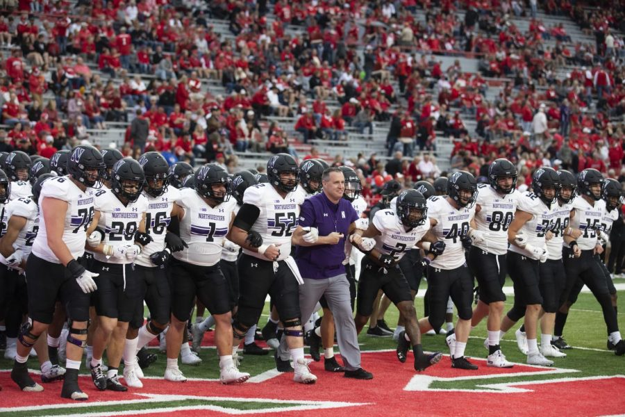 Coach in purple suit locks arms with players in white jerseys and black helmets.