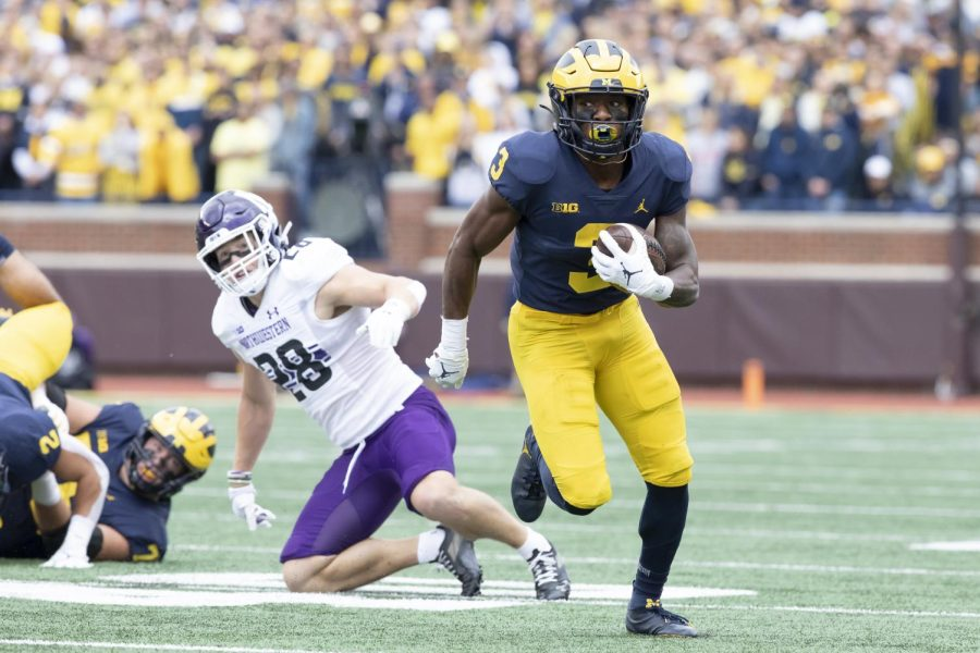 A Michigan player in a blue jersey runs with the ball along the white sideline. An NU player in a white jersey watches from the background, having fallen to the ground.