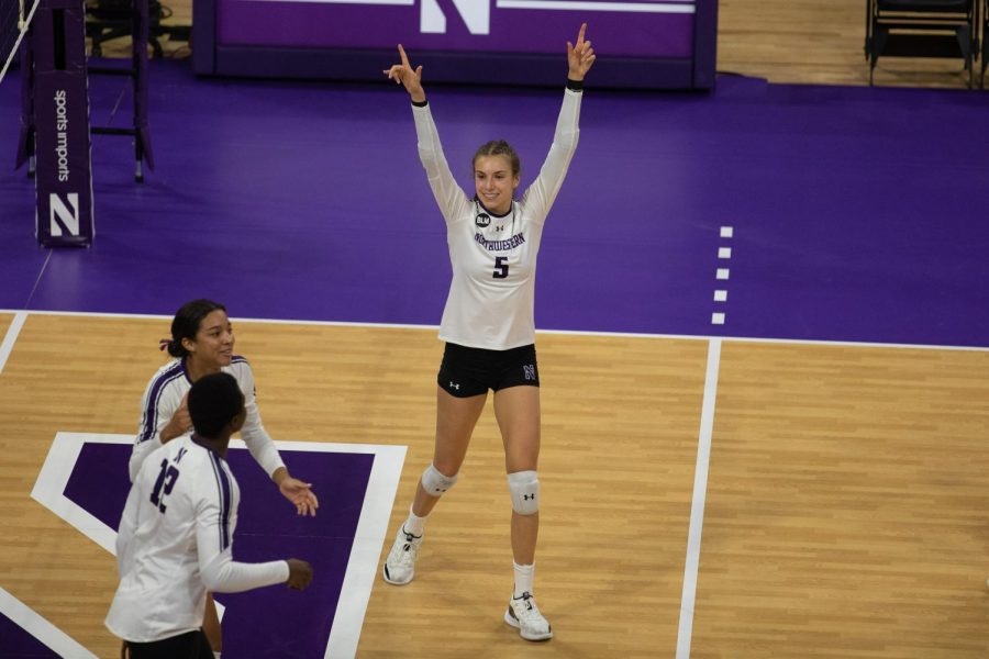 Volleyball player celebrates a point with teammates.