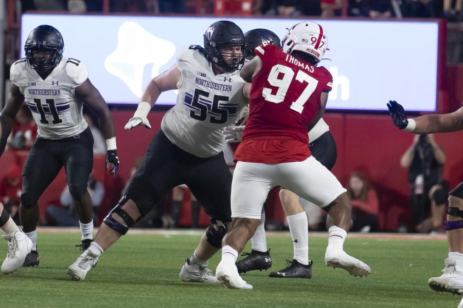 Junior right guard Conrad Rowley blocks a Nebraska defender. Rowley and three other offensive linemen injured in the contest are listed in the projected depth chart against Rutgers. Alt: Player in white jersey guards man in red jersey
