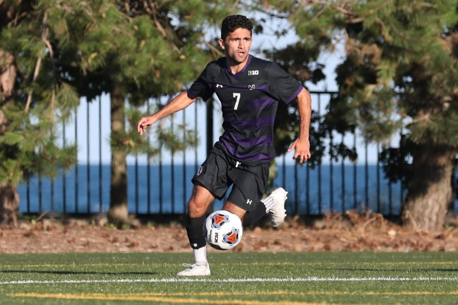A soccer player wearing a black and purple striped jersey and black shorts dribbles a soccer ball on a green field.