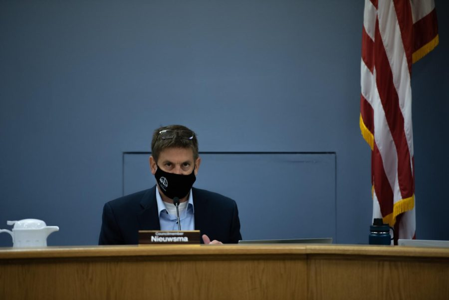 Ald. Jonathan Nieuwsma (4th) sitting at his desk with a black City of Evanston mask on.