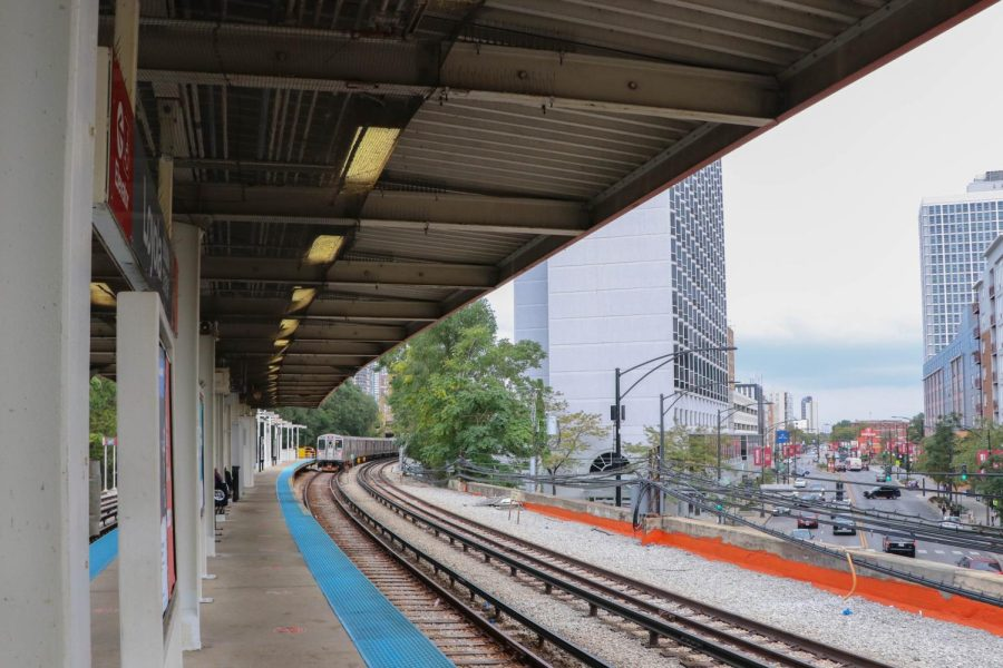 A distant train rolls into the Loyola CTA station. City buildings are visible in the distance.
