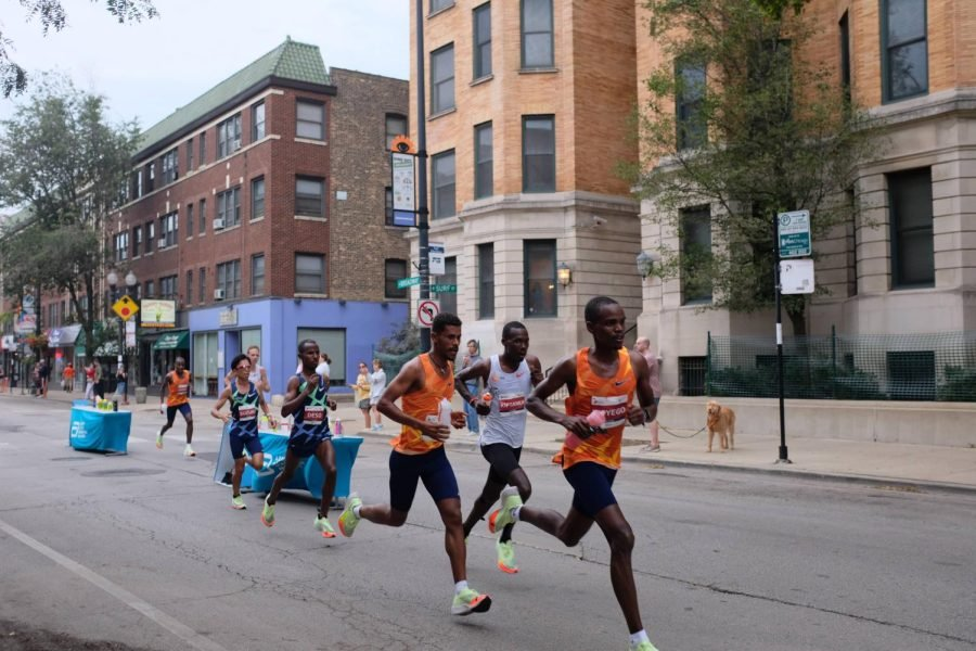 Three+people%2C+two+in+orange+tank+tops+and+one+in+a+grey+tank+top%2C+run+down+N+Broadway+as+they+are+trailed+by+other+runners.