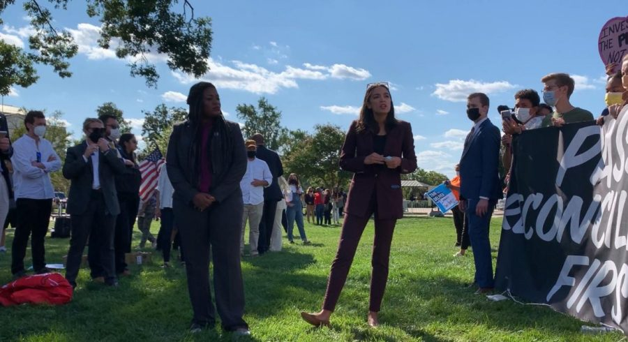 Alexandria Ocasio-Cortez speaks and Cori Bush stands to her left at an outdoor protest.