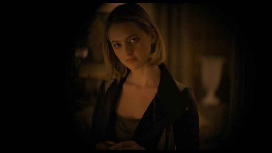 A woman in dark lighting looks directly toward the camera.