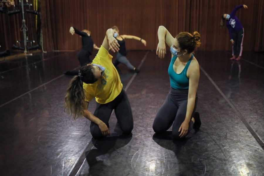 Two girls kneel on the ground and lift one arm as part of a dance routine.