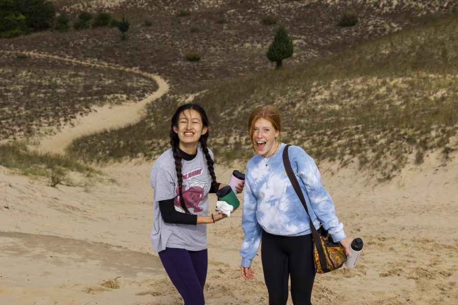 Two students dressed in long sleeves and activewear stand on a sand dune in front of brown shrubbery, smiling for a photo.