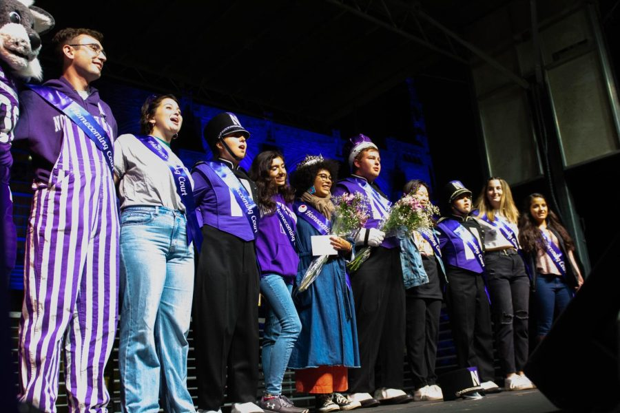 People in a row with Homecoming Court sashes stand together on a stage and the two people in the middle hold flower bouquets while wearing crowns on their heads.