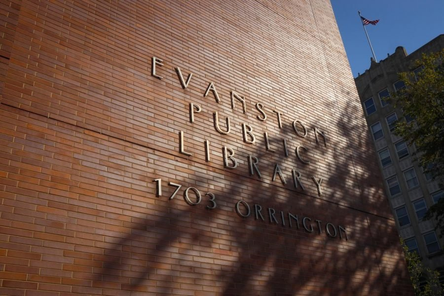 The exterior of Evanston Public Library, a red brick building. The name of EPL is on the outside in gold.