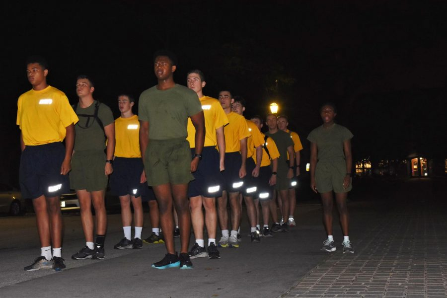 Students stand in two lines on pavement, each wearing either green or yellow T-shirts and shorts. Another student, dressed in green, stands to the side with mouth open. The sky is black.