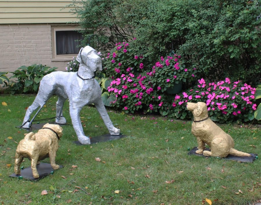 Three sculptures on grass. A silver great dane stands over a gold foil pug and beagle.