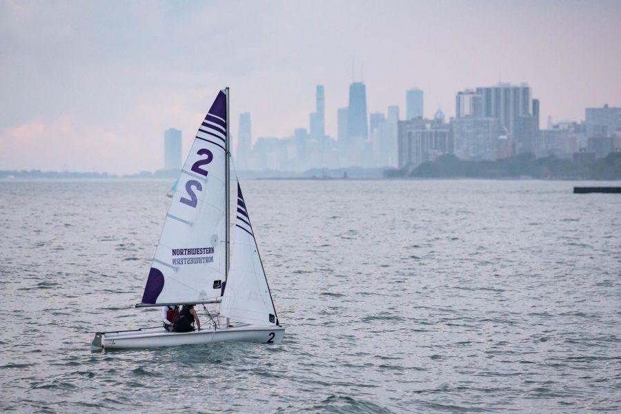 A single sailboat with the Northwestern logo floats on Lake Michigan.