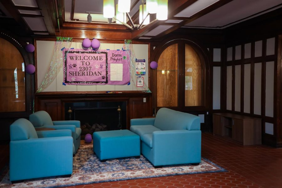 """A hardwood floor common room of a building. The room has two blue chairs and a matching blue ottoman and couch under a pink sign that reads """"Welcome to 2307 Sheridan."""""""