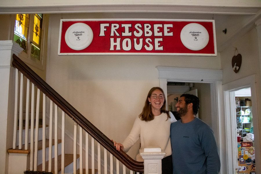 """A girl with glasses in a peach sweater and a boy with a short beard in a blue shirt laugh together at the bottom of a staircase under a red banner reading """"Frisbee House in white letters."""