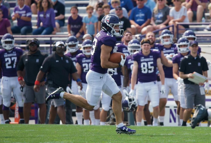 A Northwestern player runs down the field with the ball on a punt return.