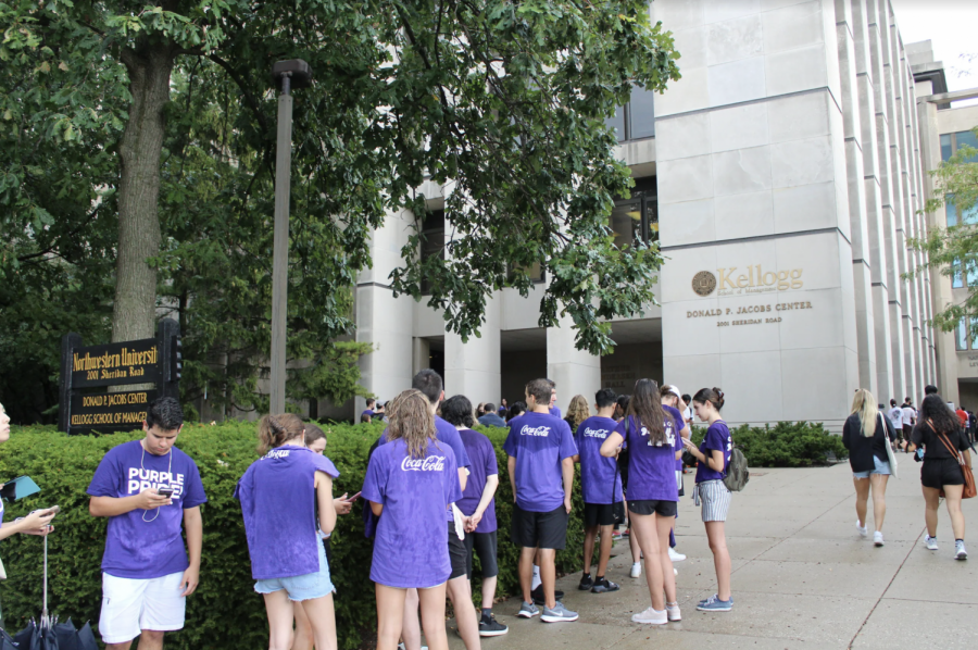 Several students in purple shirts stand in a long line in the rain in front of a tan building.