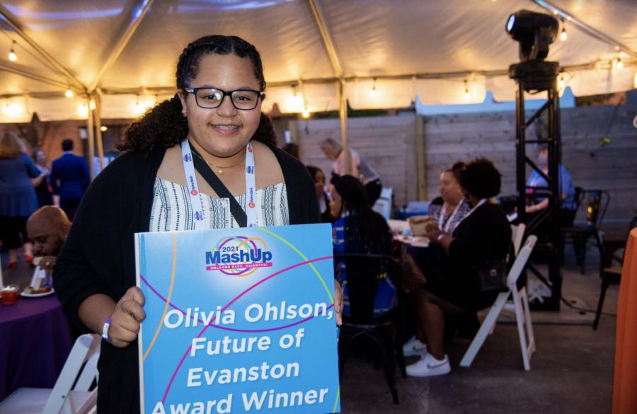 Olvia+Ohlson+smiles+while+holding+a+sign+that+says+%E2%80%9COlivia+Ohlson%2C+Future+of+Evanston+Award+Winner.%E2%80%9D