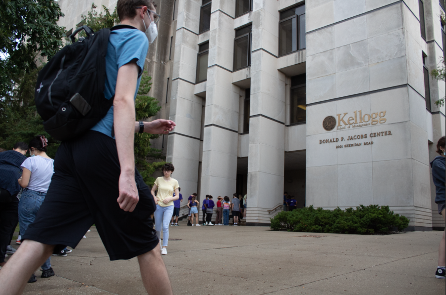 """Person in a blue shirt and black backpack walks in the direction of a tan building labeled """"Donald P. Jacobs Center."""" A line of students in several different color t-shirts stand at the building."""