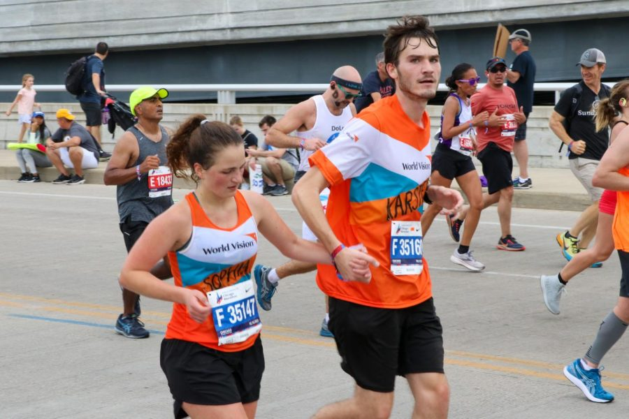 """Two runners wearing neon orange, blue and white shirts that say """"World Vision"""" hold hands as they cross a bridge."""