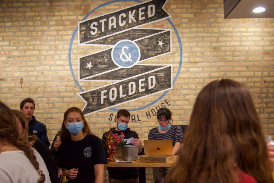 """Two individuals stand behind a table. On the table is a box that says """"Answers!"""" The Stacked & Folded logo is painted on the wall behind the individuals."""