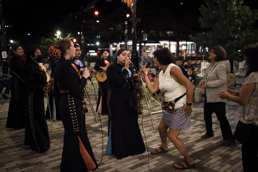 A woman in a white sleeveless shirt points to the lead mariachi singer. She is surrounded by the rest of the mariachi group.
