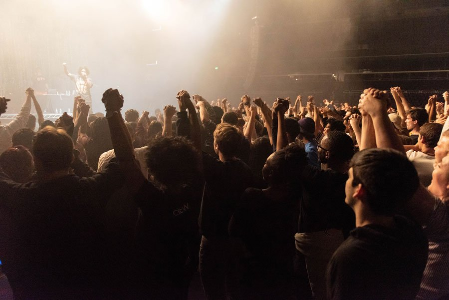 A crowd of people at a past Blowout event have their hands up in the air.