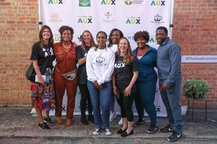 Eight people pose together in front of brick wall with banner with logos of the AUX and participating businesses.