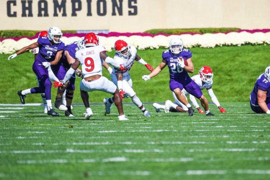 Player in purple uniform evades defender.