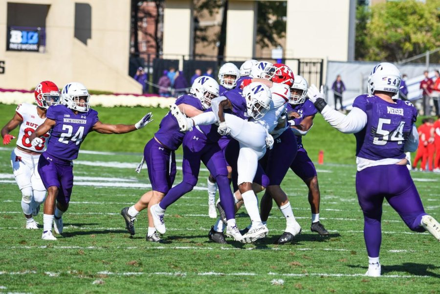 A group of players in purple football jerseys surround and tackle a player in a red jersey.