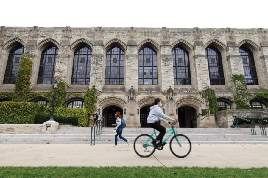 A student on a turquoise bike bikes past Deering Library as a passerby in jeans walks by in the opposite direction.