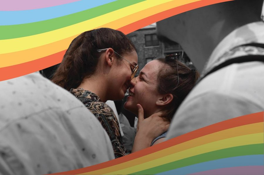 Two women embrace, their mouths nearly kissing as they smile. Rainbow flags are drawn on to the photo, framing the women.