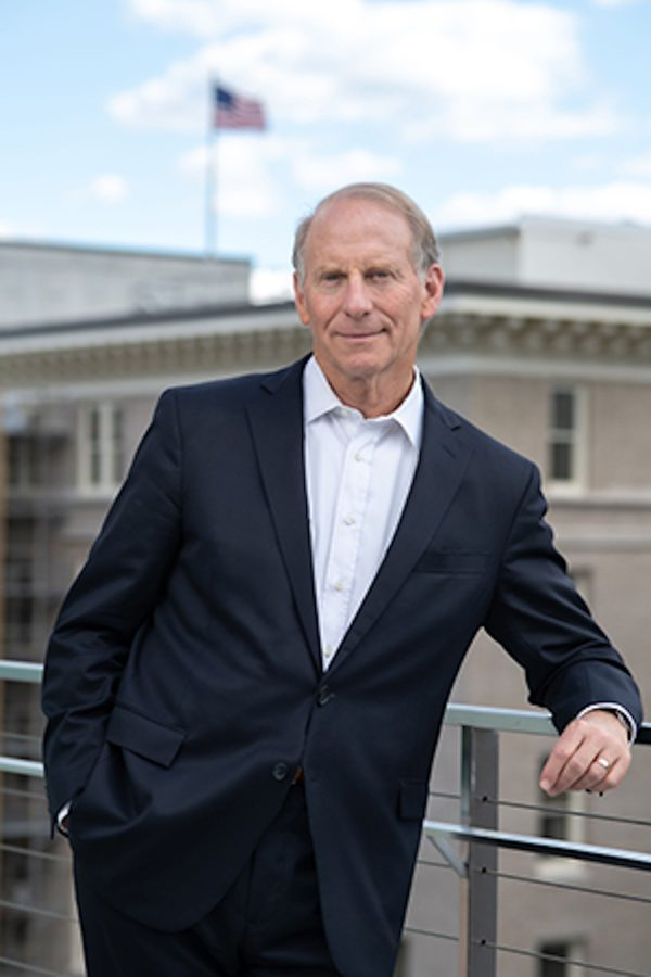 Richard Haass poses in front of a tan building.