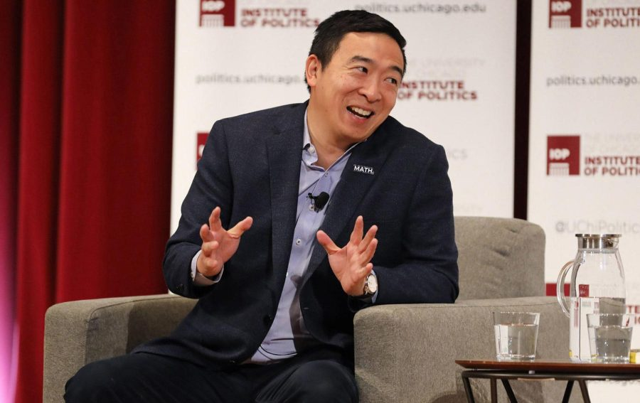 Andrew Yang speaking at an event, sitting on a grey chair next to a table with water.