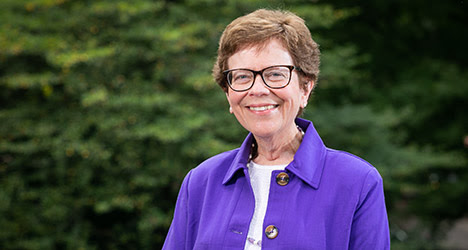 Rebecca Blank wears a white shirt and purple jacket with gold buttons, posing in front of green foliage.
