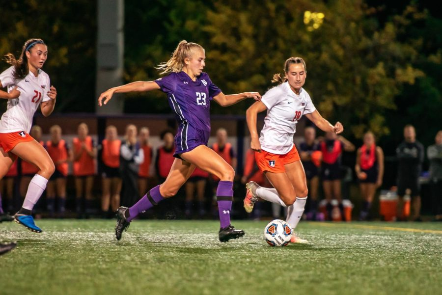 Girl with purple shirt and blond ponytail dribbles soccer ball across field between girls wearing white shirts.