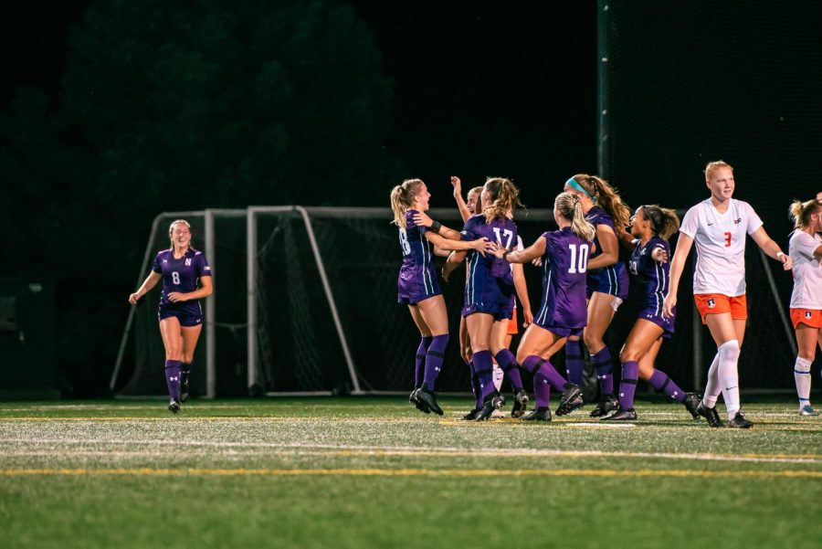 Women's soccer players celebrate after a big play.