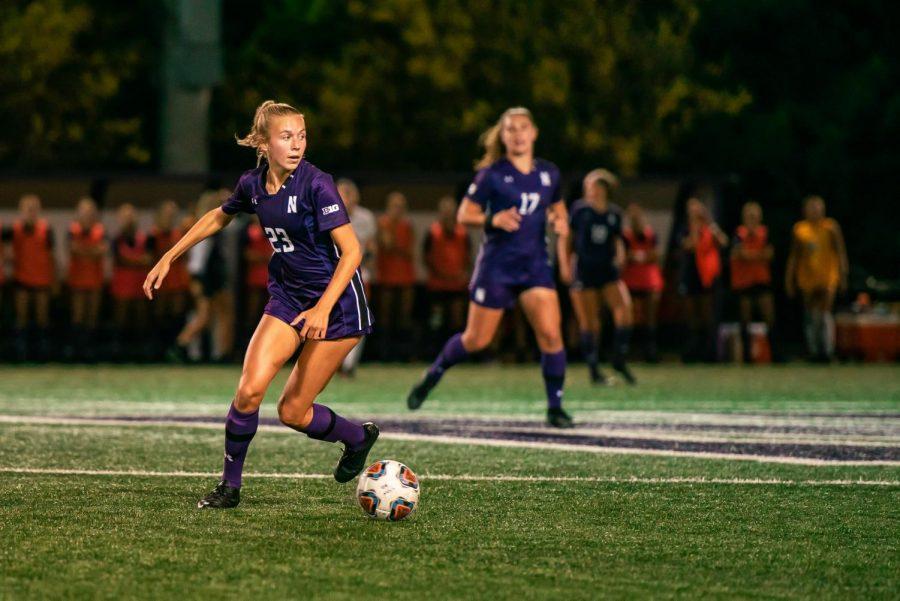 Women's soccer player dribbles ball on field.